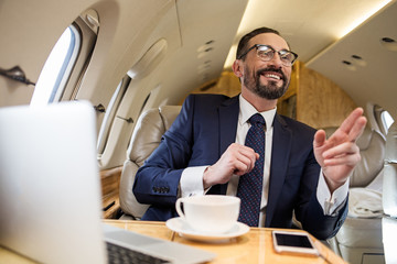Portrait of delighted bearded gentleman sitting in comfortable airplane seat looking ahead and greeting someone cheerfully