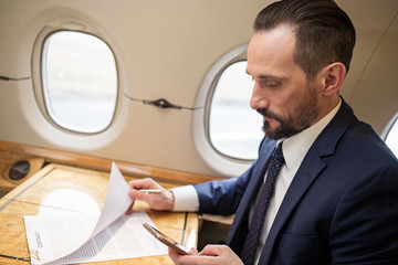 Calm stylish male sitting in aircraft seat, he is looking at his mobile phone while working with documents