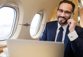 Portrait of contented gentleman in suit chatting by cellphone during his first class flight