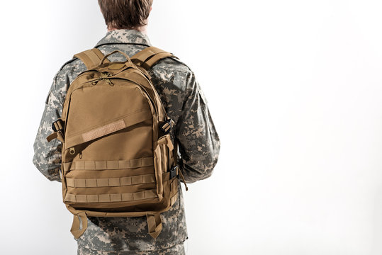 Young male soldier standing with his back turned towards the camera. He is having rucksack on his shoulders. Isolated on background. Copy space in right side
