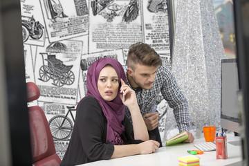 international multicultural team at work: asian muslim woman and caucasian man.