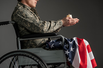 Disabled male soldier sitting in wheelchair. He is having candle in hands and usa flag on his knees. Isolated on grey background