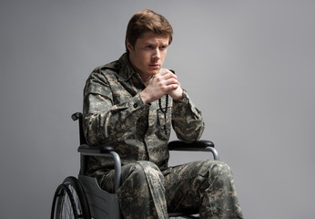 Cheerless handicapped veteran sitting in wheelchair. He is holding beads in his hands with hard look. Isolated on grey background