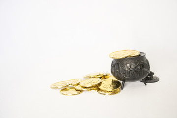Bright Gold Coins with Antique Hand Carved Irish Bog Oak Pot with Shamrocks on White Background