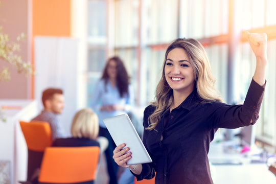 Join a digital age. Cheerful young woman holding digital tablet while his friends working on background
