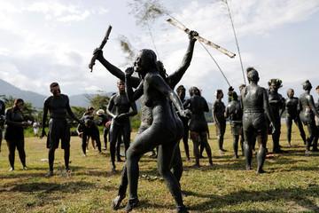 "Members of the ""Bloco da Lama"" (Block of Mud) group perform on Jabaquara beach, during a carnival festivities in Paraty"