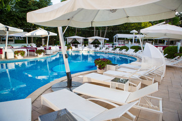 Interior of summer club with pool. Hotel pool. Resort Pool Club. Tourist resort. Pool with clean water, sun beds, folded tents, greens trees, flowers. Chaise lounges in swimming pool.
