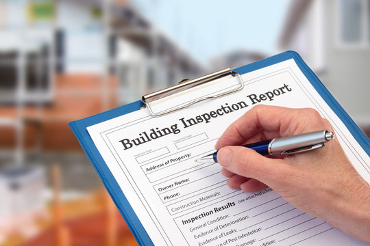 Buiding Inspector completing an inspection form on clipboard