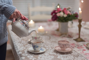 Pouring tea into vintage china teacups in the dining room