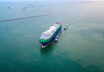 aerial view of commercial ship arrive to the port under navigating by pilot to entrance chennel due, to along terminal for cargo transmission and transport to the worldwide