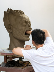 Sculptor working on his clay sculpture