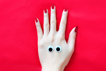 Beautiful Woman Hand with Red Nail. Red Nails Manicure Face with Eye Isolated the Red Fabric Background Great for Any Use.