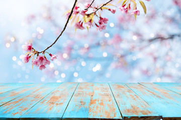 Top of wood table empty ready for your product and food display or montage with pink cherry blossom flower (sakura) on sky background in spring season.