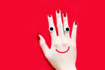 Red Nail Manicure for Valentine. Smile and Funny Face Hand with Red Nails Isolated on the Red Fabric Background Great for Any Use.