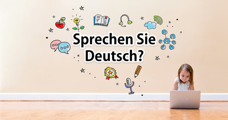 Sprechen Sie Deusch text with little girl using a laptop computer on floor