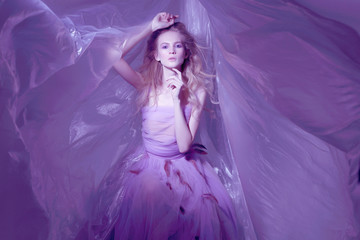 Fashion portrait of young beautiful woman in fluffy violet dress.