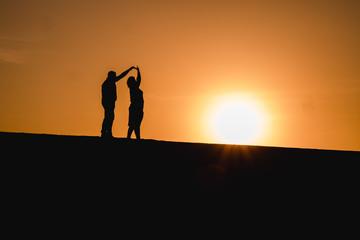Silhouetten von einem Paar das bei Sonnenuntergang tanzt