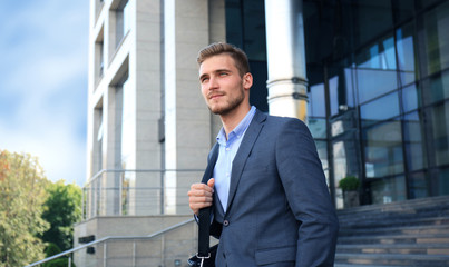 Portrait of a handsome businessman in a suit standing outside a city building.