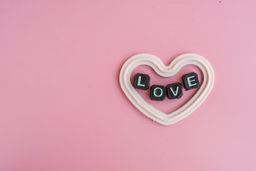 white chocolate in heart shape with message love on pink background, valentine concept.