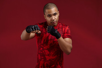 Picture of determined young athletic male of mixed race appearance exercising in gym, wearing stylish t-shirt and boxing bandages, mastering punching techniques. Sports, fitness and workout