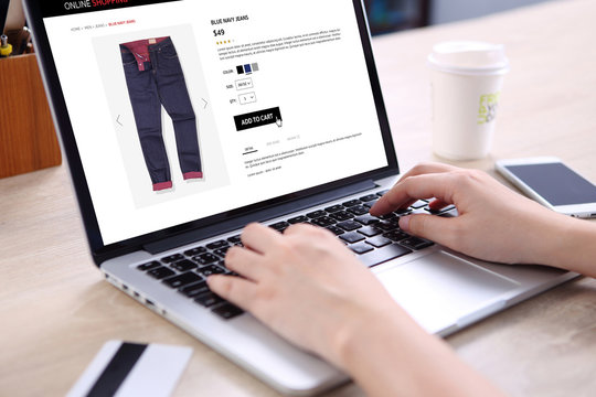 People buying blue navy jeans on ecommerce website with smart phone, credit card and coffee on wooden desk
