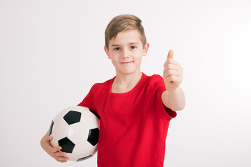 boy in red shirt with soccer ball and thumb up