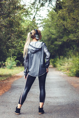 beautiful young girl walking on a park,  listening to music on headphones.