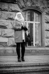 Closeup of beautiful mature woman having a walk in city. Stylish middle age woman wearing coat and scarf at cold weather, outdoor shot.