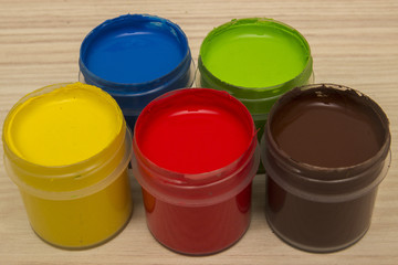 Finger paints in jars on a wooden background