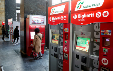 A passenger buys a train ticket at the self-service ticket machine at the Santa Lucia Station in Florence
