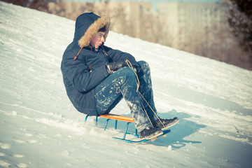 Guy have fun in the winter, ride sled from a snowy mountain. Snow Mountain, Male and Sledge. Guy spend time cheerfully in the winter