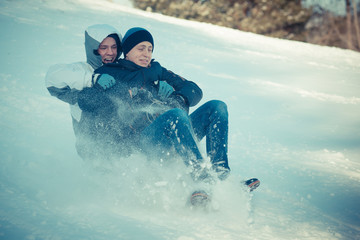 Guys have fun in the winter. Friends ride sled from a snowy mountain. Snow Mountain, Male and Sledge. Guy spends time cheerfully in the winter