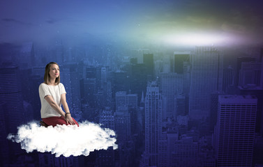 Woman sitting on cloud above the city