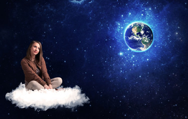 Woman sitting on cloud looking at planet earth