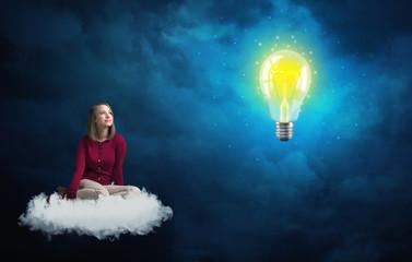 Woman sitting on a cloud lokking at huge lightbulb