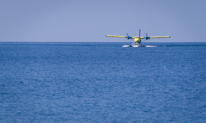 Private seaplane landing in the ocean lagoon.