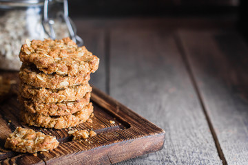 Tuinposter Koekjes Homemade oatmeal cookies on wooden board on old table background. Healthy Food Snack Concept. COpy space/