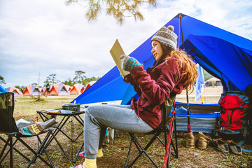 Asian women travel relax camping in the holiday. camping on the Mountain. sit relax read a book In the chair. Thailand