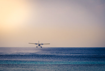 Private seaplane taking off in the ocean lagoon.