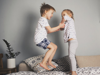Pretty kids jumping on the bed together