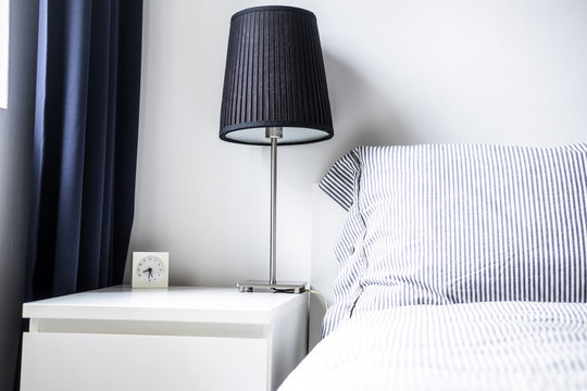 White gray bedroom design ideas. Minimalist comfort style. Night table, lamp, bed with linen striped pillows and blanket, dark curtain. Copy space, horizontal