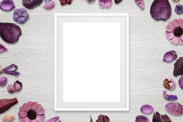Picture frame with isolated white space for picture or text. Flower decorations around the frame. White wooden desk in background. Top view.