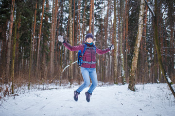 Photo of jumping woman with backpack walking in winter forest