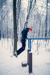Image of sports man on horizontal bar in winter at woods