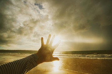 A man's hand against the sunset and ocean background. Storm landscape and people.