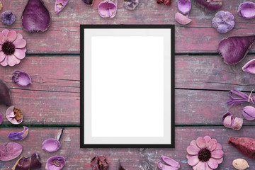 Picture frame on pink wooden desk surrounded with flower decorations. Top view.