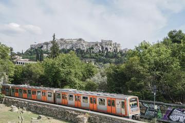 Train passes Monastiraki with Acropolis hill view in Athens, Greece
