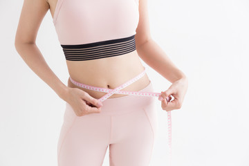 Asian woman with measure tape in her hand to measure herself,Healthy lifestyles concept of body