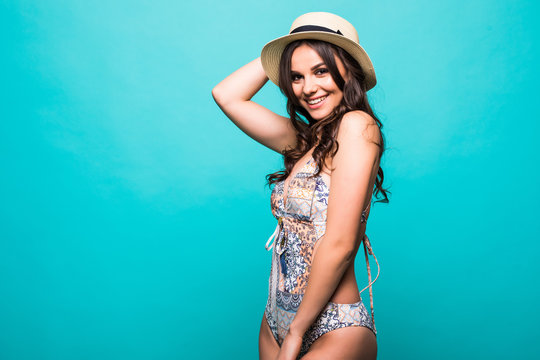 Portrait of female wearing bikini, hat isolated on green. Concept of summer holidays and traveling