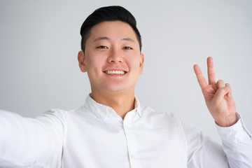 Selfie of Happy Asian Guy with Peace Gesture